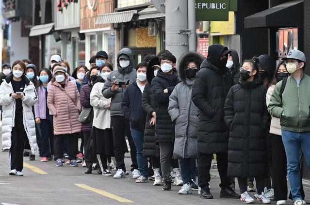 People wait in line to buy face masks from a store at the Dongseongro shopping district in Daegu on February 27, 2020. South Korea reported 334 new coronavirus cases on February 27, taking its total to 1,595, still the largest in the world outside China, where the disease first emerged. (Photo by Jung Yeon-je/AFP Photo)