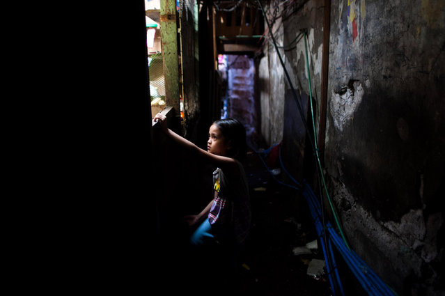 A girl buys candy at a makeshift store inside an informal settlers community on August 11, 2014 in Manila, Philippines. (Photo by Dondi Tawatao/Getty Images)