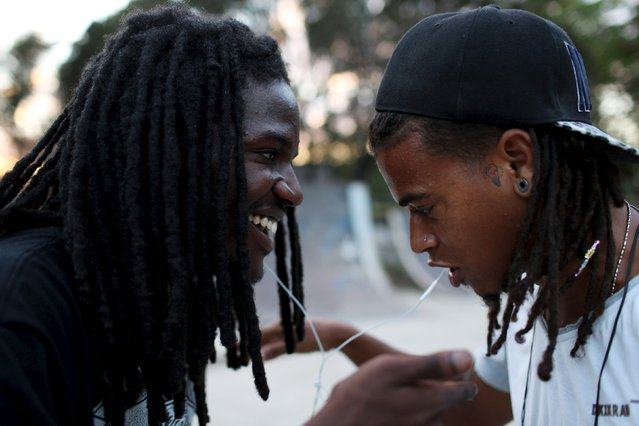 U.S. singer Ramsey Aburdene, 26, (L), sings hip-hop with tattoo shop owner Felipe Suni, 23, in Havana, March 18, 2015. (Photo by Alexandre Meneghini/Reuters)