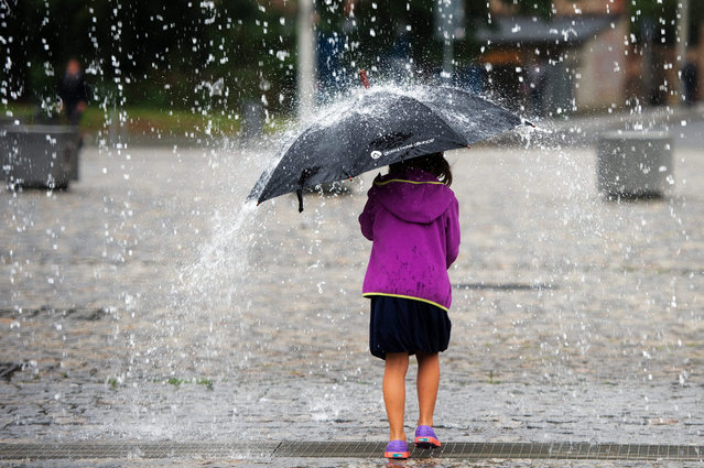 """A girl from New York tests her umbrella in the """"Waterscreen"""", an art installation by German artist Rainer Splitt, in Dresden, Germany, 19 August 2015. The water sculpture stands on the thearer square in the city center. (Photo by Arno Burgi/EPA)"""