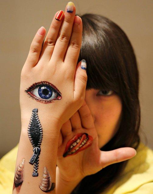 Musashino Art University student Kana Ogawara displays body paintings by Hikaru Cho on her hands at an art event in Tokyo, Sunday, August 10, 2014. (Photo by Shizuo Kambayashi/AP Photo)