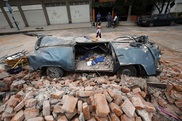 A van sits in a pile of rubble after it was smashed by a wall that collapsed during a massive earthquake, in Mexico City, Friday September 8, 2017. One of the most powerful earthquakes ever to strike Mexico hit off its southern Pacific coast, killing at least 35 people, toppling houses, government offices and businesses. Mexico's capital escaped major damage, but the quake terrified sleeping residents, many of whom still remember the catastrophic 1985 earthquake that killed thousands and devastated large parts of the city. (Photo by Marco Ugarte/AP Photo)