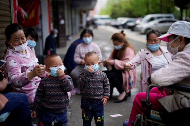 Children and women wearing face masks are seen in Xianning, after the lockdown was eased in Hubei province, the epicentre of China's coronavirus disease (COVID-19) outbreak, March 26, 2020. (Photo by Aly Song/Reuters)