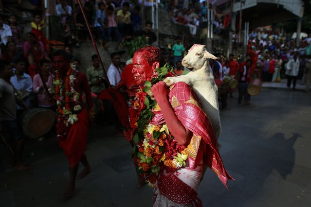 A Hindu priest, face smeared with color and sacrificial blood, carries a goat for sacrifice during the Deodhani festival at the Kamakhya Hindu temple in Gauhati, India, Monday, August 18, 2014. During this festival devotees sacrifice goats and pigeons. (Photo by Anupam Nath/AP Photo)