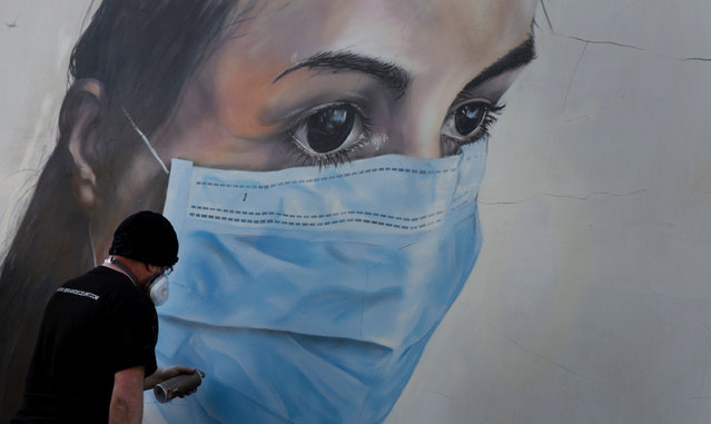 Graffiti artist Bram De Ceurt works on a street graffiti piece of a nurse with a mouth mask to protect against coronavirus in Antwerp, Belgium, Thursday, March 26, 2020. (Photo by Virginia Mayo/AP Photo)