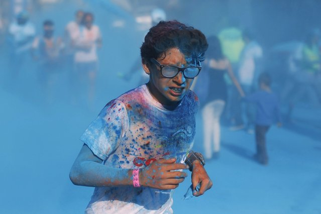 A participant runs through colored powder while taking part in the Color Run race in Tegucigalpa, August 30, 2015. The five-kilometre (3.11 miles) race aims to promote a healthy lifestyle and will help to raise funds for the Department of Pediatrics of a public hospital, according to local media. (Photo by Jorge Cabrera/Reuters)