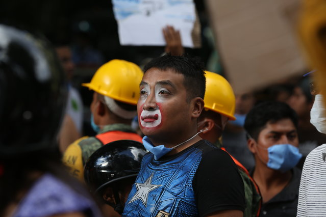 A street clown arrives to help the the recovery and search of victims at a collapsed building after a 7.1 earthquake in Mexico City, Tuesday, September 19, 2017. (Photo by Gustavo Martinez Contreras/AP Photo)