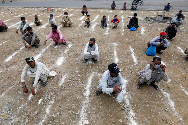 Men sit on the ground with lines drawn with chalk to maintain safe distance as they wait to receive sacks of ration handouts from a distribution point of a charity welfare during a partial lockdown after Pakistan shut all markets, public places and discouraged large gatherings amid an outbreak of coronavirus disease (COVID-19), in Karachi, Pakistan, March 26, 2020. (Photo by Akhtar Soomro/Reuters)