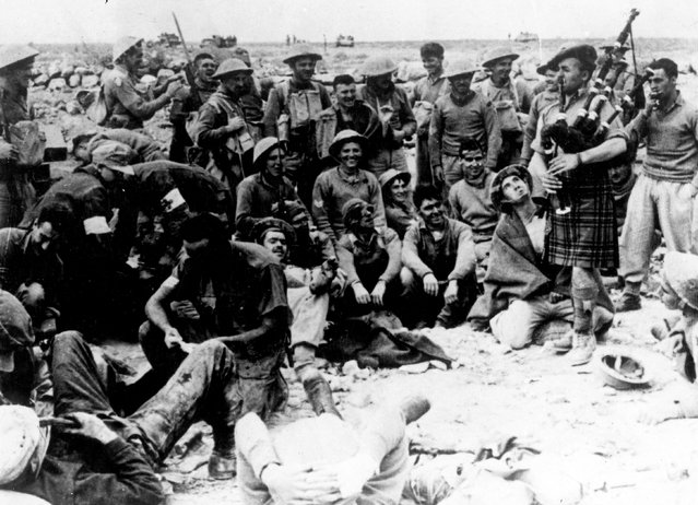 Soldiers being entertained by an officer playing the bagpipes at their camp in Libya, North Africa, during the Second World War, circa 1940. (Photo by Keystone)