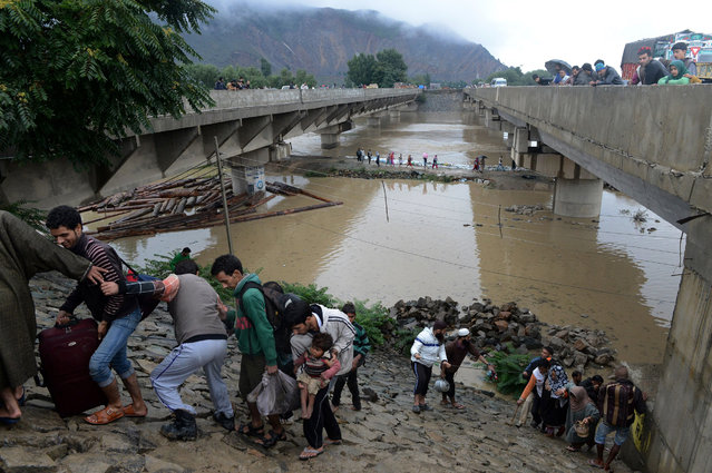 Kashmiri residents walk along an embankment on the side of a bridge as they head for a higher ground during flooding on the outskirts of Srinagar on September 6, 2014. More than 200 people in Pakistan and northern India have been killed in torrential monsoon rains which triggered flooding, landslides and house collapses, officials in the two countries said September 6. (Photo by Tauseef Mustafa/AFP Photo)