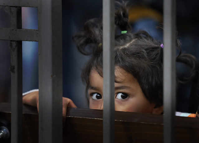 A child traveling with other asylum-seekers waits for a train to leave for the Hungarian border with Austria at Keleti train station in Budapest, Hungary, Sunday, September 6, 2015. Over 150,000 people seeking to enter Europe have reached Hungary this year, most coming through the southern border with Serbia, and many apply for asylum but quickly try to leave for wealthier EU countries. (Photo by Frank Augstein/AP Photo)