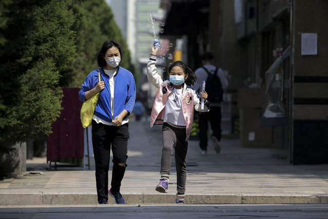 A child wearing a protective face mask to help curb the spread of the new coronavirus plays with bubbles next to a masked woman as they walk along a pavement in Beijing, Tuesday, April 28, 2020. The Chinese city of Wuhan that was the original epicenter of the pandemic again reported no new coronavirus cases or deaths Tuesday and its hospitals remained empty of virus patients for a second straight day. (Photo by Andy Wong/AP Photo)