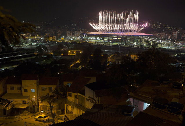 The Mangueira slum is backdropped by fireworks exploding above the Maracana stadium during the opening ceremony of the Rio's 2016 Summer Olympics in Rio de Janeiro in Rio de Janeiro, Brazil, Friday, August 5, 2016. (Photo by Leo Correa/AP Photo)