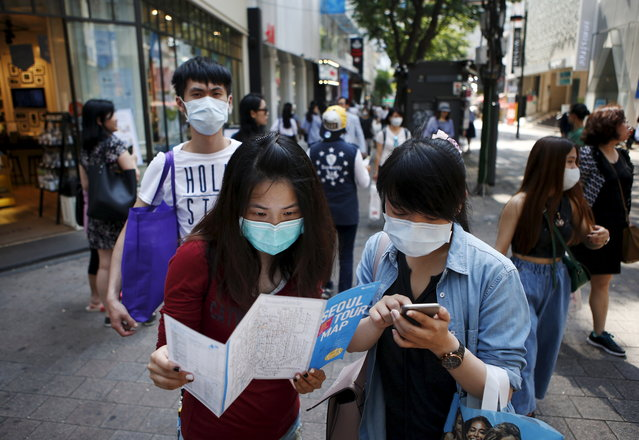 Tourists wearing masks to prevent contracting MERS look at a tour map of Seoul at Myeongdong shopping district, in central Seoul, South Korea, June 10, 2015. (Photo by Kim Hong-Ji/Reuters)