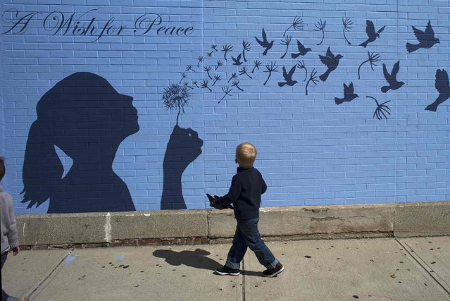 """A boy looks up at a mural reading """"A Wish for Peace"""" in Medford, Massachusetts September 15, 2014. (Photo by Brian Snyder/Reuters)"""