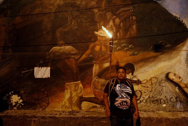 A demonstrator holds a torch as he stands in front of a mural during a march to demand the resignation of Honduras' President Juan Orlando Hernandez in Tegucigalpa, September 11, 2015. (Photo by Jorge Cabrera/Reuters)