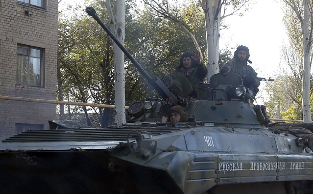"An  pro-Russian rebel armored personal carrier with an inscription reading: ""Russian Orthodox Christian Army"" passes through the town of Donetsk, eastern Ukraine, Thursday, October 2, 2014. Pro-Russian rebels in eastern Ukraine advanced Wednesday on the government-held airport in Donetsk, pressing to seize the key transportation hub even as the two sides bargained over a troop pullout under a much-violated truce. (Photo by Darko Vojinovic/AP Photo)"