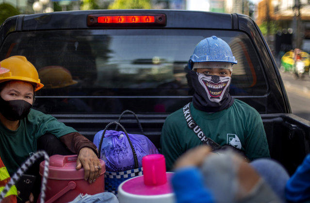 Construction workers wearing face masks travel in a back of a crew cab in Bangkok, Thailand, Wednesday, May 13, 2020. Thai government continue to ease restrictions related to running business in capital Bangkok that were imposed weeks ago to combat the spread of COVID-19. (Photo by Gemunu Amarasinghe/AP Photo)