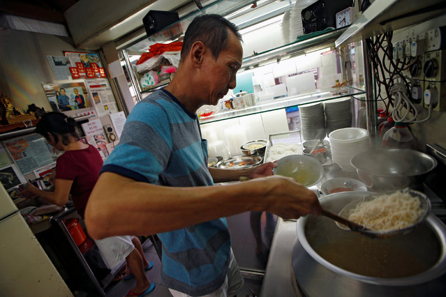 "Hawker Lim Swee Heng prepares a bowl of laksa noodles, at Roxy Laksa stall, at the East Coast Lagoon Food Village in Singapore August 8, 2016. ""It takes years to get the right balance to the broth, to make it thick just add coconut, to make it watery just add water, but to go in-between, to get that right balance – that's the hard work of my dish"". (Photo by Edgar Su/Reuters)"