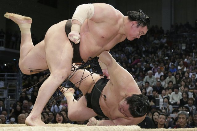 Yokozuna-ranked sumo wrestler Hakuho of Mongolia (top) throws Goeido of Japan during their bout on the final day of the 15-day Kyushu Grand Sumo Tournament in Fukuoka on November 26, 2017. Mongolian grand champion Hakuho won the latest sumo tournament on November 25 as Japan's national sport continued to draw media attention after another top wrestler faced a police probe into an alleged assault. He won the 15-day tournament at 13-1 by Saturday with one day remaining as his closest contenders were all defeated at 11-3 before his bout on the day. (Photo by AFP Photo/JIJI Press)