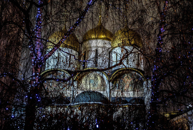 A Kremlin cathedral is seen behind iluminated trees in downtown Moscow on November 29, 2017. (Photo by Mladen Antonov/AFP Photo)
