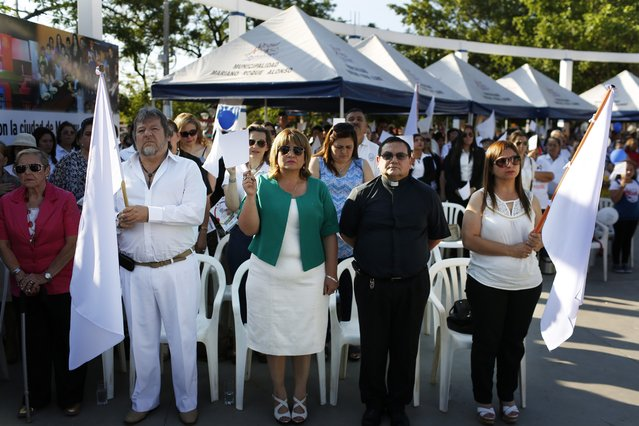 """In this October 28, 2017 photo, Mayor Carolina Aranda, center holding a white flag, is accompanied by members of the Catholic church during a pro-Life ceremony in Mariano Roque Alonsno, Paraguay. """"We don't support same-s*x marriage because it's not natural, and we oppose that in our schools they teach our boys and girls that being gay, trans or lesbian is a choice"""", said Aranda. (Photo by Jorge Saenz/AP Photo)"""