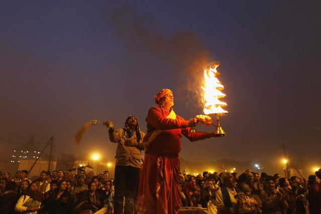 "A Hindu priest holds an oil lamp as he performs evening prayers near the banks of river Ganges ahead of the ""Kumbh Mela"" (Pitcher Festival) in the northern Indian city of Allahabad January 12, 2013. During the festival, Hindus take part in a religious gathering on the banks of the river Ganges. ""Kumbh Mela"" will return to Allahabad in 12 years. (Photo by Ahmad Masood/Reuters)"