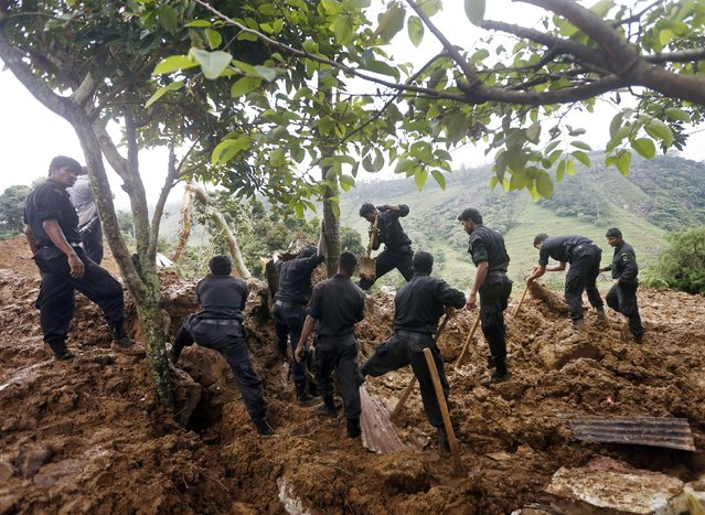 Members of a rescue team conduct a search at the site of a landslide at the Koslanda tea plantation near Haldummulla October 30, 2014. (Photo by Dinuka Liyanawatte/Reuters)