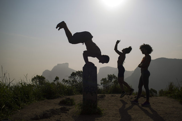 People exercise on the Morro Dois Irmaos or Two Brothers Mountain, atop the Vidigal slum in Rio de Janeiro, Brazil, Friday, October 2, 2015. Despite the recent wave of violence in other pacified favelas, Vidigal has been peaceful and is today a popular tourist spot. (Photo by Felipe Dana/AP Photo)