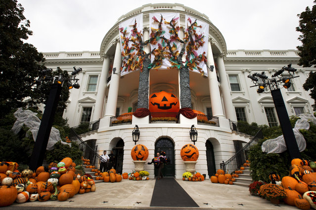 """A White House usher takes a model of one of the Obama dogs outside as Halloween decorations adorn the South Portico of the White House in Washington, Friday, October 31, 2014, ahead of festivities for trick-or-treaters. President Barack Obama and first lady Michelle Obama will welcome local children and children of military families to """"trick-or-treat"""" at the White House for Halloween. (Photo by Jacquelyn Martin/AP Photo)"""