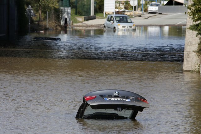 An abandoned car is submerged in deep water near by an underpass after flooding caused by torrential rain in Mandelieu, France, October 4, 2015. (Photo by Eric Gaillard/Reuters)