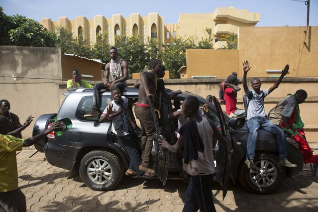 Anti-government protesters drive a car belonging to a member of parliament outside the parliament building in Ouagadougou, capital of Burkina Faso, October 30, 2014. (Photo by Joe Penney/Reuters)