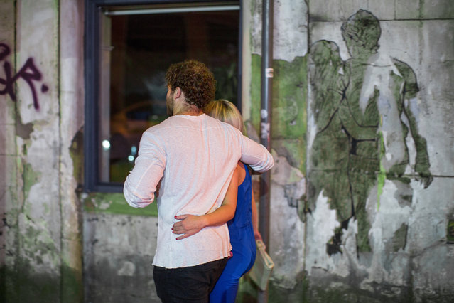 A couple walk arm in arm past pasted street art of a couple walking arm in arm on Dantzic Street in Manchester, UK on September 11, 2016. (Photo by Joel Goodman/London News Pictures)