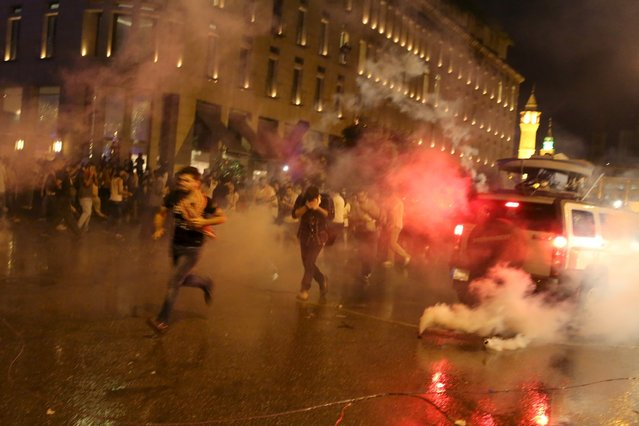 Protesters run from tear gas fired by security forces in Martyr square, downtown Beirut, Lebanon October 8, 2015. (Photo by Aziz Taher/Reuters)