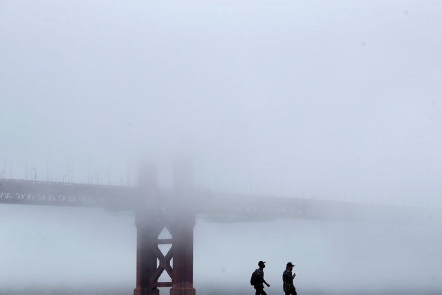 A man wears a face mask while walking on a pier in front of the Golden Gate Bridge during the coronavirus outbreak in San Francisco, Saturday, May 16, 2020. (Photo by Jeff Chiu/AP Photo)