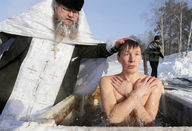 Priest Sergei Ryzhov conducts a ceremony as a man takes a dip in the freezing waters of Lake Buzim during Orthodox Epiphany celebrations near the village of Sukhobuzimskoye north of Krasnoyarsk, Russia on January 19, 2018. (Photo by Ilya Naymushin/Reuters)