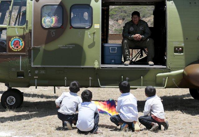 "Children talk with a member of Bolivian super puma helicopter crew in Vila Vila where Bolivia's President Evo Morales and U.N. Secretary-General Ban Ki-Moon inaugurated a sports arena called ""Coliseo Ban Ki-Moon"", south of Cochabamba, October 11, 2015. (Photo by David Mercado/Reuters)"