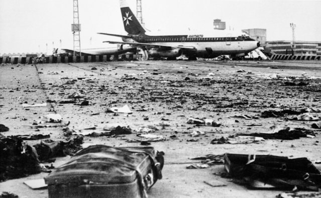 Pieces of suitcases and debris are scattered over the tarmac at Cairo international Airport, Egypt after two bombs that were in a suitcase exploded after being unloaded on October 13, 1981. The plane originated in Libya, with a stop over in Malta, before arriving in Cairo. (Photo by AP Photo/Donina)