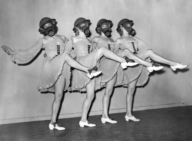 Dancers at the Windmill Theatre in London, practice a routine wearing gas masks and hard-hats with their costumes, 1940. (Photo by Hulton Archive/Getty Images)