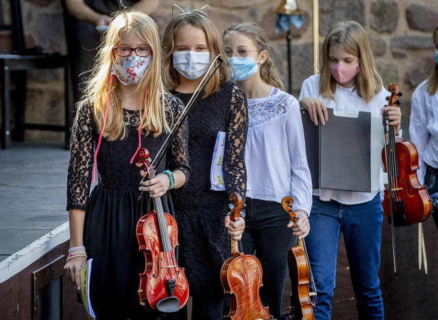Young violinists wear face masks on the way to their music school concert in the old castle in Bad Vilbel near Frankfurt, Germany, Sunday, September 20, 2020. (Photo by Michael Probst/AP Photo)