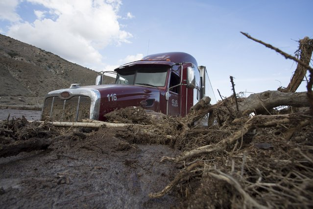 A truck remains mired in mud and debris on State Route 58 near Tehachapi, California, about 60 miles (97 km) outside of Los Angeles October 17, 2015. (Photo by David McNew/Reuters)