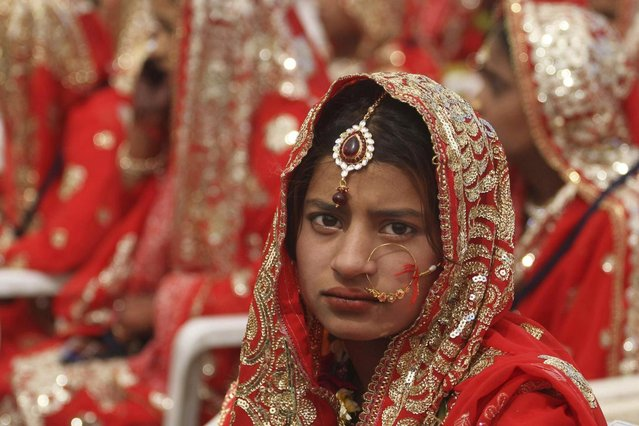 An Indian bride, sits during a mass marriage of 162 Muslim couples in Ahmadabad, India, Sunday, March 3, 2013. Mass marriages in India are organized by social organizations primarily to help the economically backward families who cannot afford the high ceremony costs as well as the customary dowry and expensive gifts that are still prevalent in many communities. (Photo by Ajit Solanki/AP Photo/LaPresse)