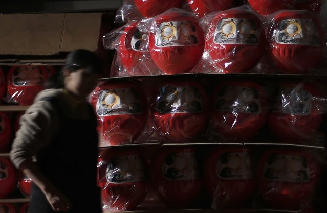"""A staff walks past Daruma dolls, which is believed to bring good luck, as she works at a stockpile of Daruma shop  """"Daimonya"""" in Takasaki, northwest of Tokyo November 23, 2014. (Photo by Yuya Shino/Reuters)"""