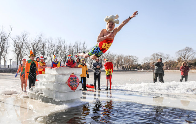 A swimming enthusiast in festive attire jumps into cold river at Beiling Park on the first day of Spring Festival on February 16, 2018 in Shenyang, Liaoning Province of China. The cold water on the frozen Beiling Park couldn't stop the enthusiasm of a group of winter swimming enthusiasts. (Photo by VCG/VCG via Getty Images)