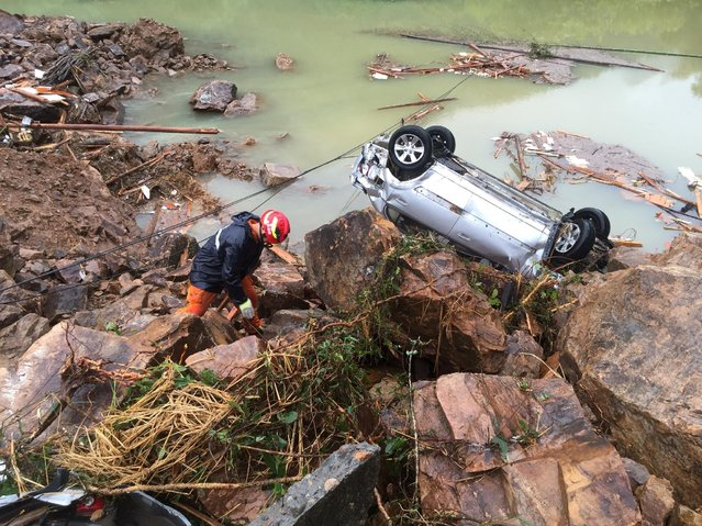 A rescue worker is seen next to an overturned car at the site of a landslide caused by heavy rains brought by Typhoon Megi, in Sucun Village, Lishui, Zhejiang province, China, September 29, 2016. (Photo by Reuters/Stringer)