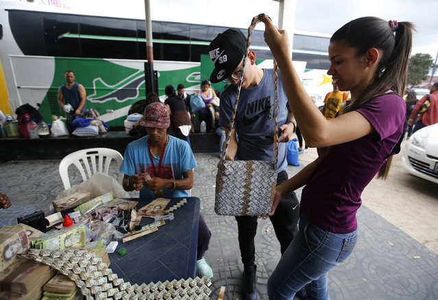 In this February 22, 2018 photo, a couple looks at a bag made out of Venezuelan Bolivars in La Parada, Colombia, on the border with Venezuela. Each collector item produced by Richard Segovia, sitting at the table, fetches between $10 and $15 – a huge markup from the pennies that bolivars retrieve on Venezuela's black market. (Photo by Fernando Vergara/AP Photo)