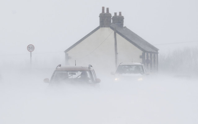 Motorists drive through snow blown from fields near Buxton in central England March 22, 2013. Heavy snowfalls caused disruption across the country on Friday. (Photo by Darren Staples/Reuters)
