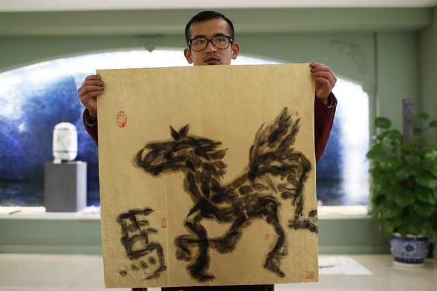 Folk artist Han Xiaoming shows his completed artwork of a horse painted entirely with his tongue in Hangzhou, Zhejiang province December 4, 2014. (Photo by Aly Song/Reuters)