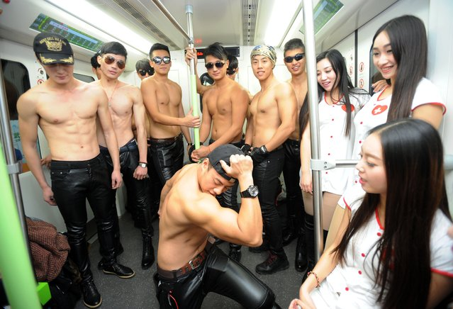 Chinese aids activists hand out condoms in a subway train in Wuhan, central China's Hubei province on December 1, 2014. The World Health Organization issued a call to action to China on December 1, 2014 over HIV/AIDS as government figures said nearly half a million people are living with the disease or its precursor, with hundreds of thousands more thought to be undiagnosed. (Photo by AFP Photo)