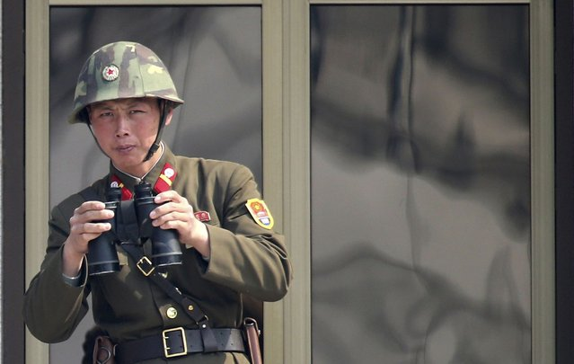 """A North Korean soldier watches the South Korean side at the border village of Panmunjom in the demilitarized zone (DMZ) in South Korea Thursday, April 4, 2013. South Korea's defense minister said Thursday North Korea has moved a missile with """"considerable range"""" to its east coast, but said it is not capable of hitting the United States. (Photo by Lee Jong-hoon/AP Photo/Yonhap)"""